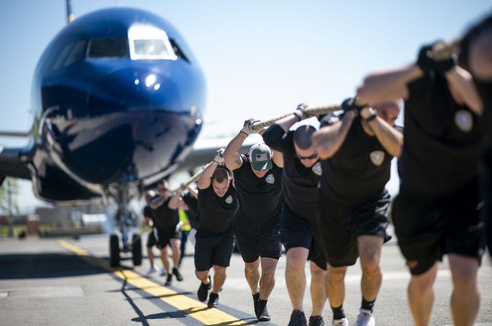 Participantes da competição anual Plane Pull puxando um JetBlue A320 no Aeroporto Internacional John F. Kennedy, em Nova York, EUA