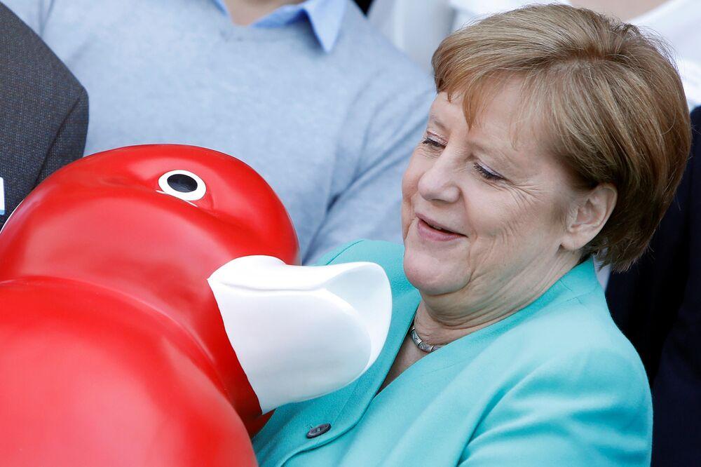 Chanceler alemã Angela Merkel recebe um presente ao visitar a empresa de biotecnologia Centogene em Rostock, Alemanha, 23 de maio de 2019