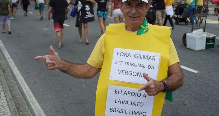 Apoiador do presidente Jair Bolsonaro é fotografado usando placa com frases críticas ao ministro do STF, Gilmar Mendes.