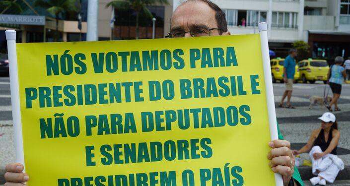 Apoiador do presidente Jair Bolsonaro carrega cartaz com críticas ao Congresso.