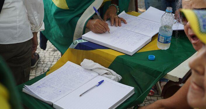 Manifestantes em Copacabana coletam assinaturas pelo fechamento do Supremo Tribunal Federal.
