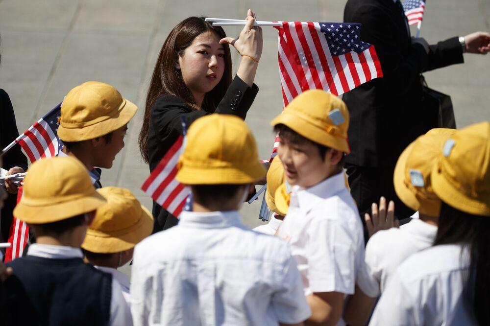 Estudantes japoneses com bandeiras americanas se preparando para a chegada de Trump ao Palácio Imperial em Tóquio