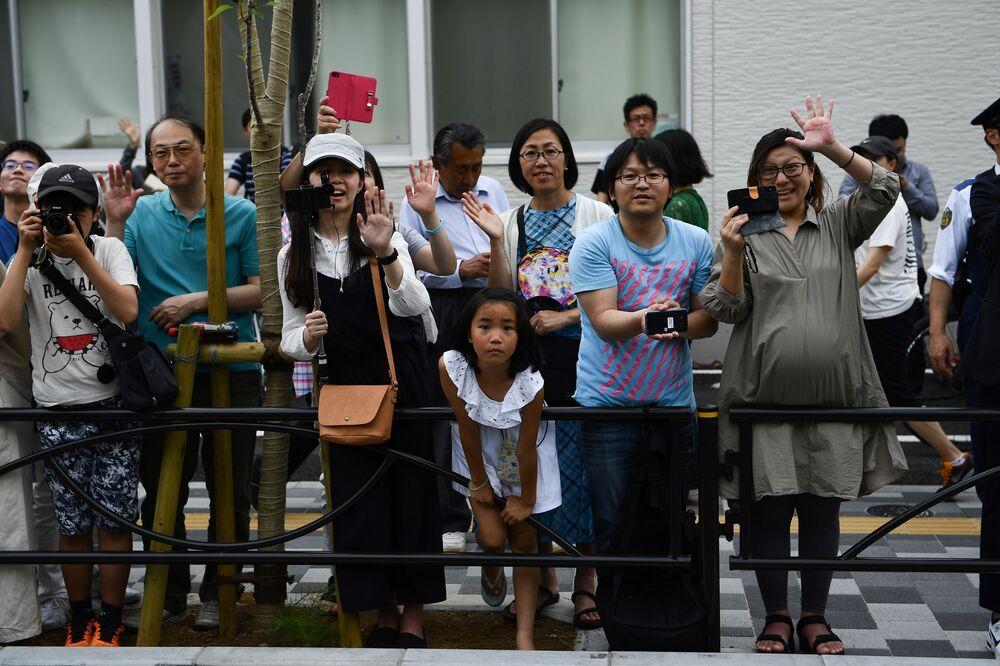 Espectadores ao longo do trajeto do cortejo com o presidente Donald Trump em Tóquio