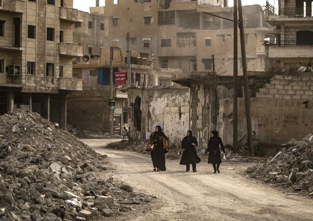 Mulheres caminham em meio a ruínas em Raqqa, cidade localizada no norte da Síria, 1º de maio de 2019