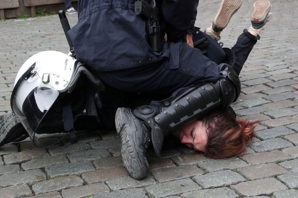 Policial detém uma manifestante dos coletes amarelos no decurso dos protestos em Bruxelas, no último dia das eleições para o Parlamento Europeu