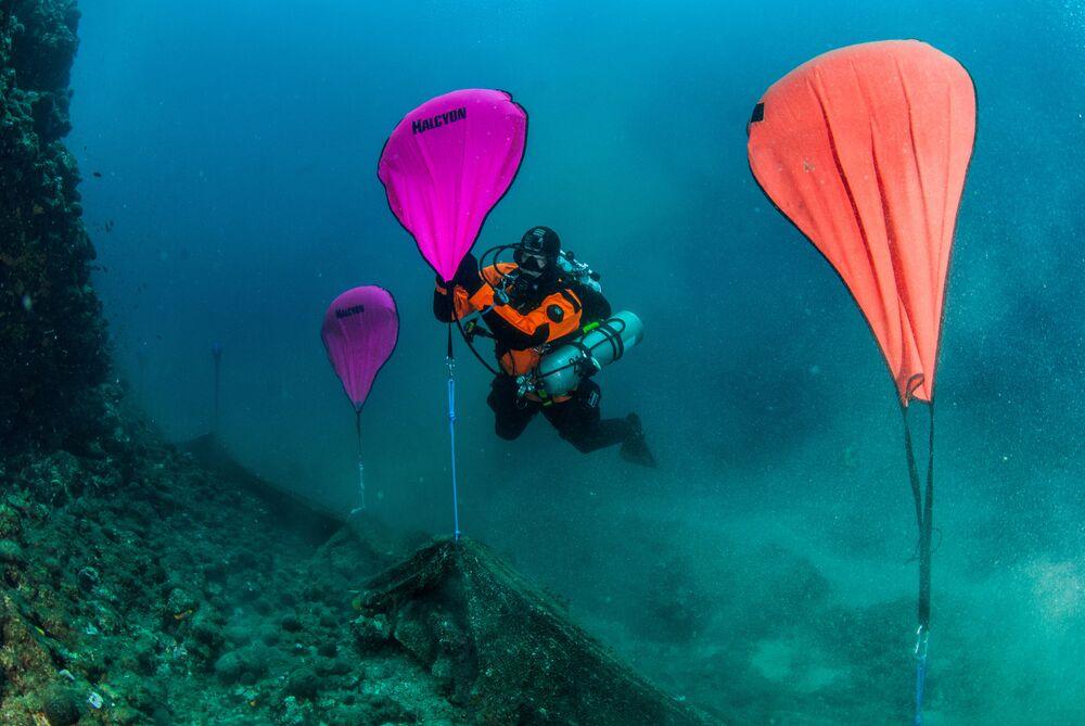 Mergulhadores limpam o lixo e redes de pesca do fundo marinho perto de Calcídica, Grécia