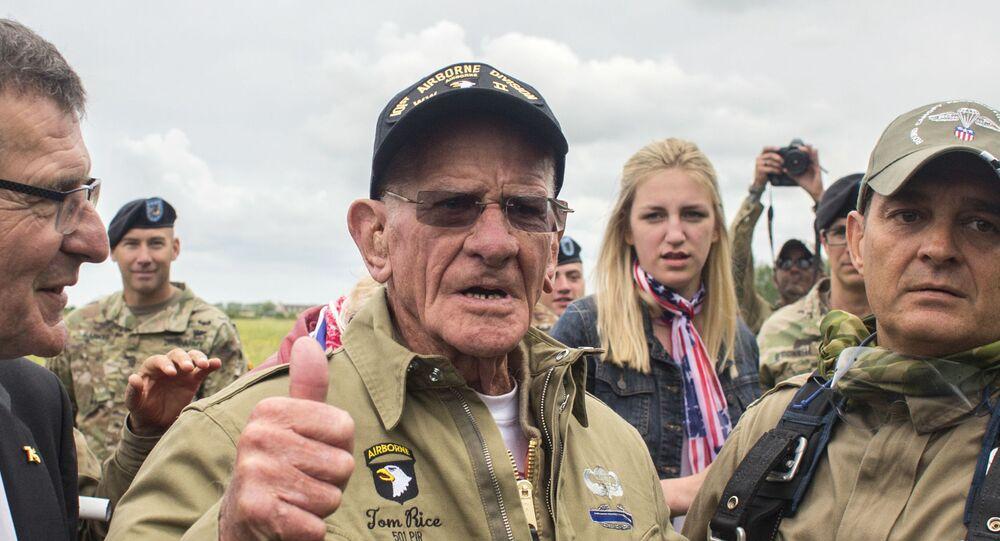 Tom Rice, veterano de 97 anos do exército dos EUA, faz sinal de positivo após refazer salto de paraquedas que realizou no Dia D, em 1944.