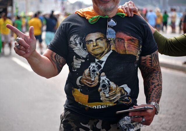 Manifestante veste camisa com imagem de Bolsonaro apontando armas durante protesto pró-governo, Rio de Janeiro, 26 de maio de 2019
