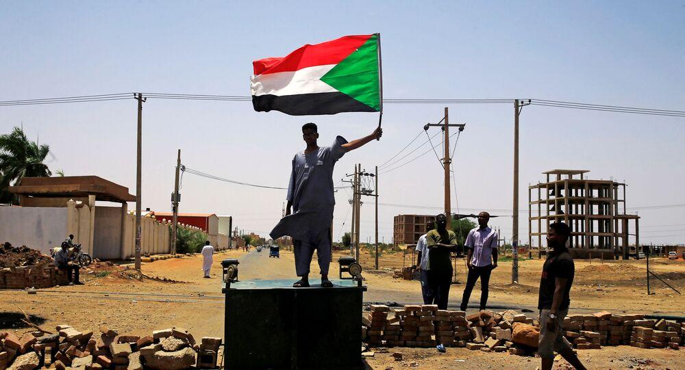 Um manifestante sudanês em Cartum segura uma bandeira nacional ao se deparar com uma barricada ao longo de uma rua, exigindo que o Conselho Militar de Transição do país entregue o poder a civis.