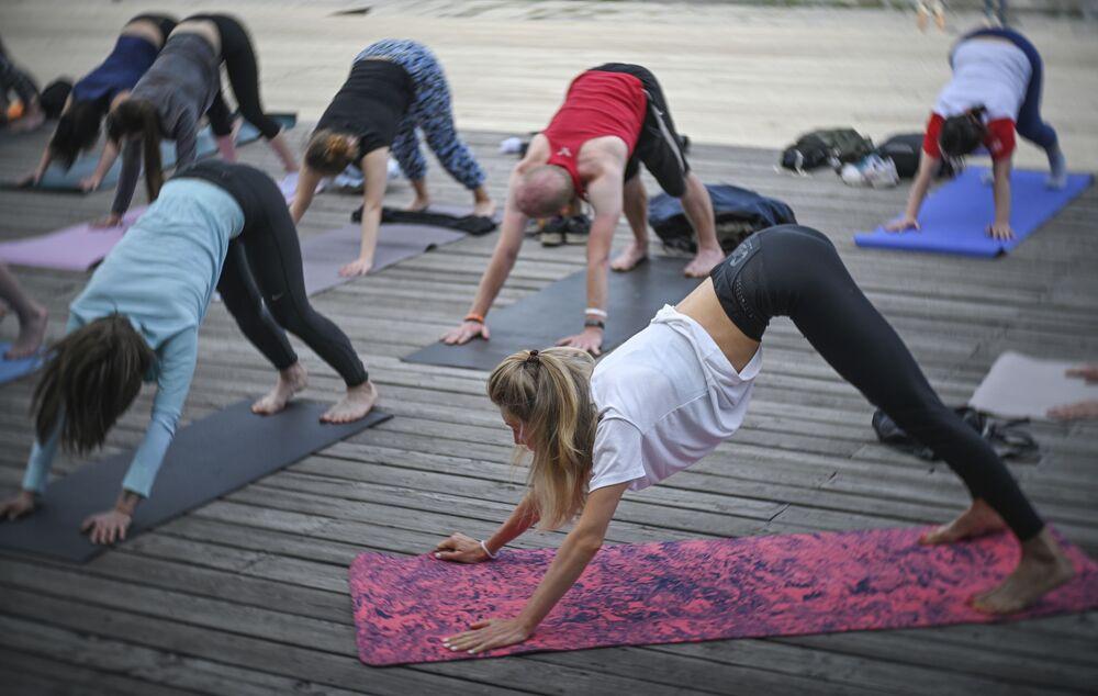 Participantes do projeto Yoga em Parques durante o treino em um parque de Moscou, Rússia