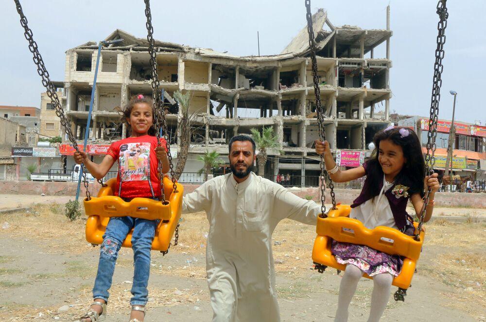 Meninas brincam perto de edifício danificado no primeiro dia do feriado muçulmano Eid al-Fitr, em Raqqah, Síria