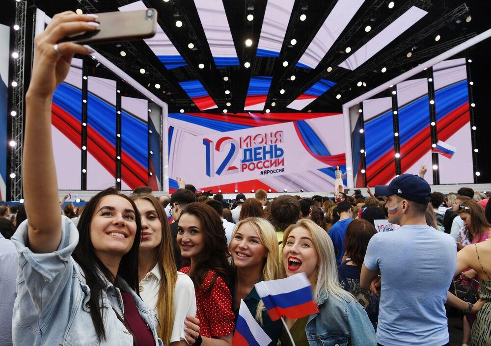 Jovens tiram foto durante show na Praça Vermelha, em Moscou, por ocasião do Dia da Rússia