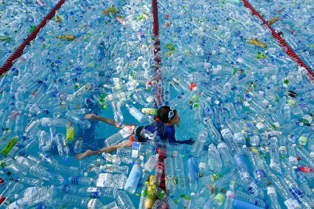 Criança nada em piscina cheia de garrafas de plástico durante uma campanha de sensibilização para assinalar o Dia Mundial dos Oceanos em Bangkok, 8 de junho de 2019