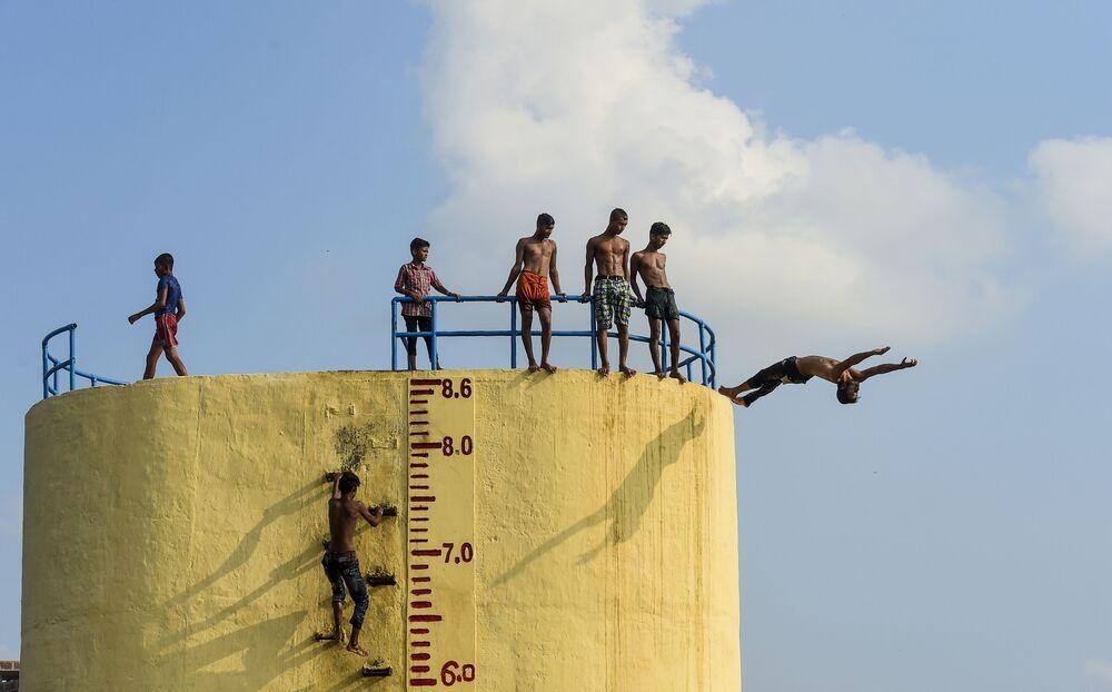 Jovens pulando no rio Buriganga em um dia quente de verão em Daca, Bangladesh