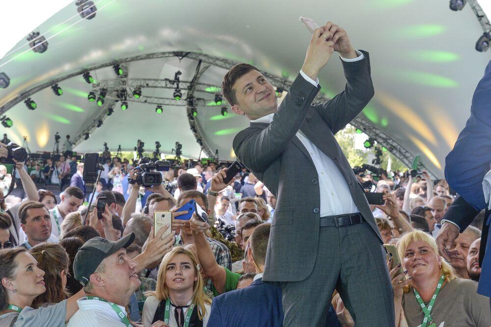 Presidente da Ucrânia, Vladimir Zelenski, tira fotos durante o primeiro congresso de seu partido no jardim botânico da cidade, Kiev, Ucrânia