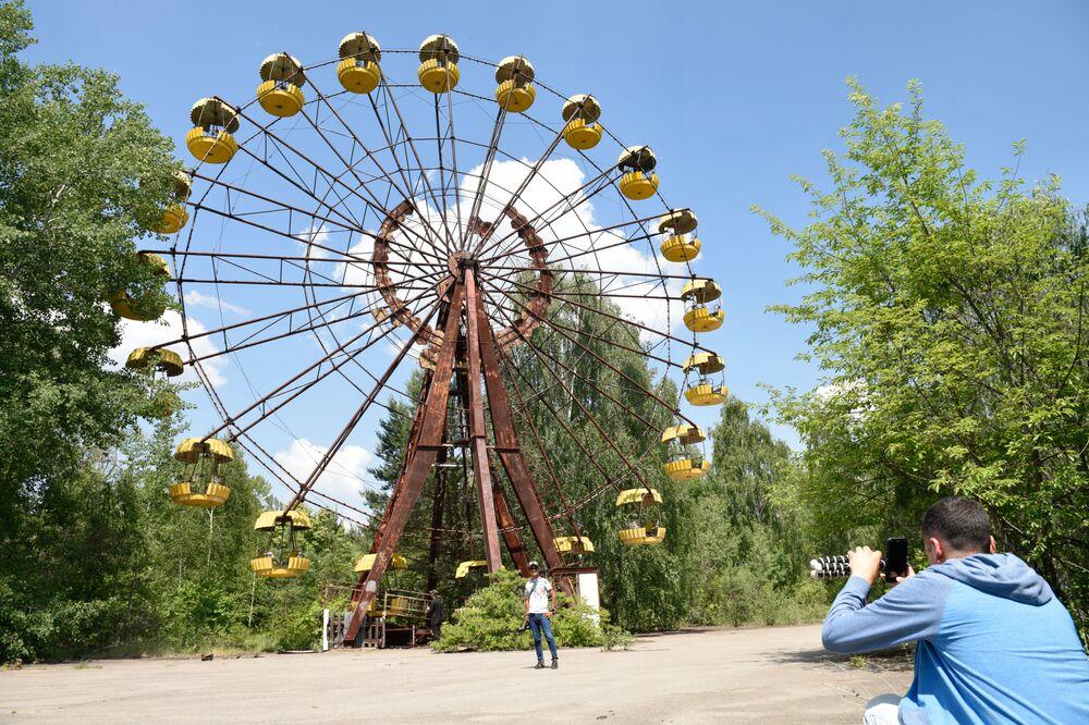 Turistas durante uma excursão à zona de exclusão da usina nuclear de Chernobyl na cidade de Pripyat, Ucrânia