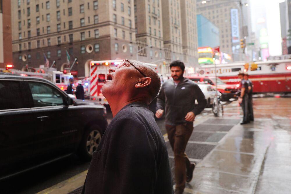 Homem observa local da queda de helicóptero em arranha-céus em Nova York, nos EUA, 10 de junho de 2019