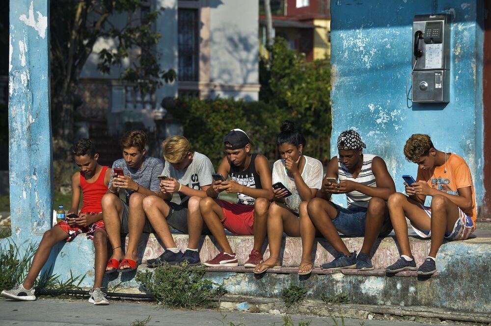 Jovens cubanos com telefones celulares em rua de Havana