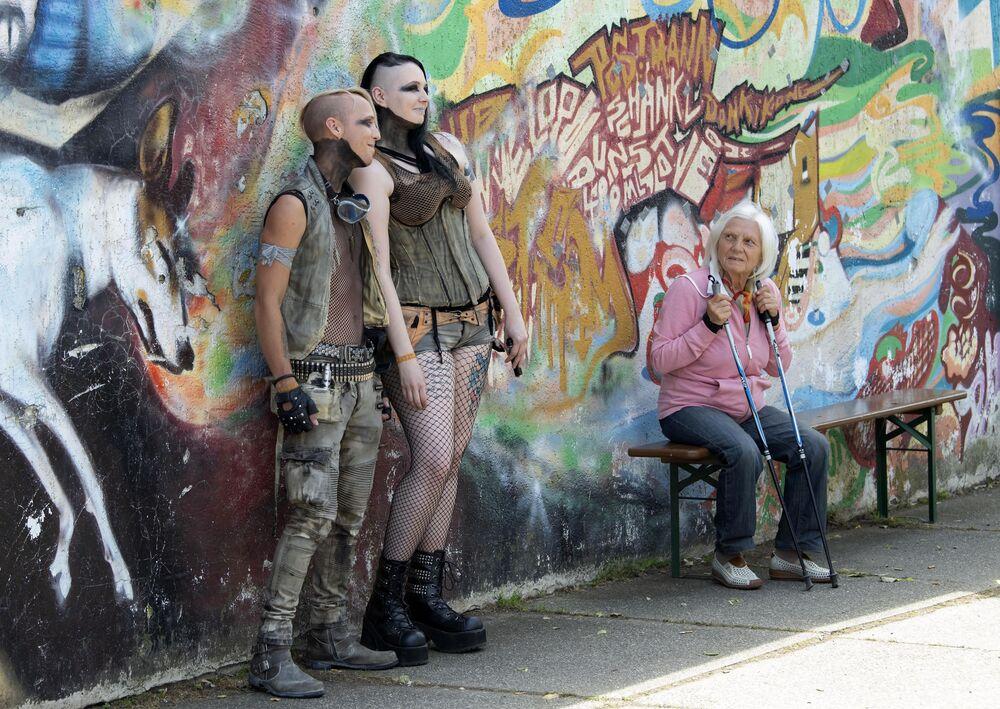 Pessoas são fotografadas perto de parede grafitada durante o festival gótico anual em Leipzig, na Alemanha