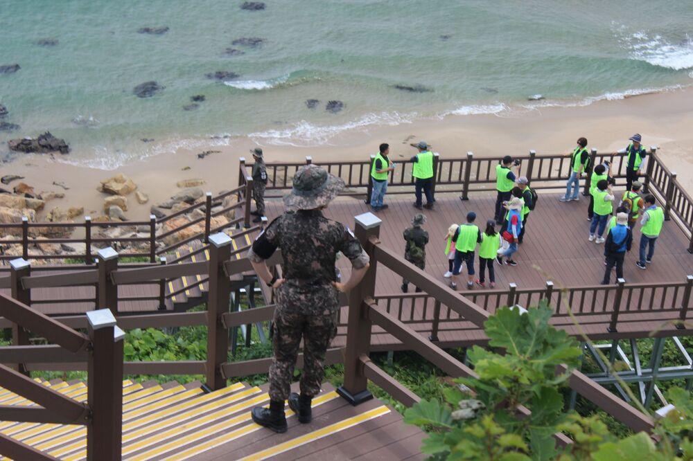 Participantes da excursão tiram fotos sob supervisão da polícia militar