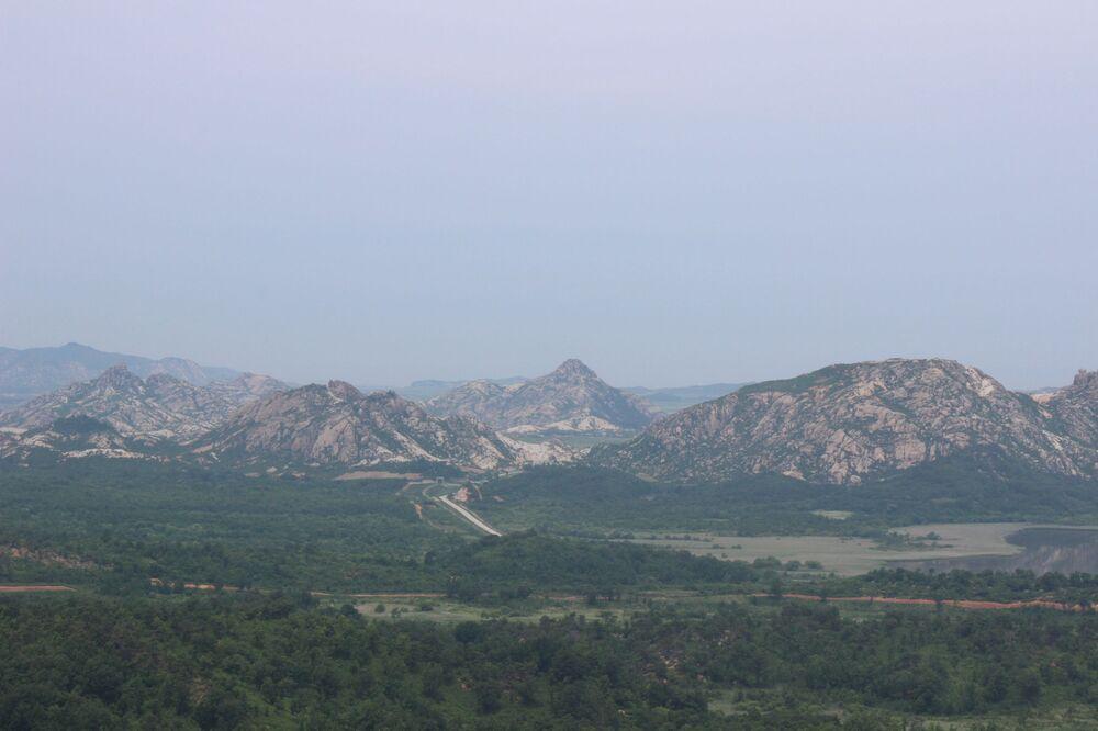 Vista do mirante mais setentrional da Coreia do Sul sobre a estrada que atravessa a fronteira. O pequeno arco entre as montanhas é a porta de entrada na Coreia do Norte