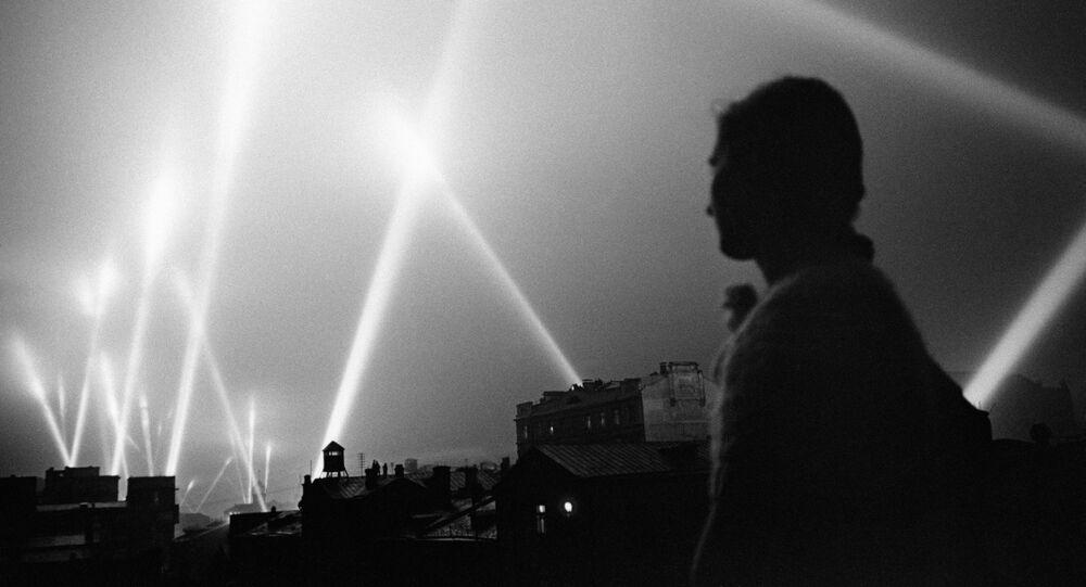 Feixes de luz dos holofotes da defesa antiaérea iluminam o céu de Moscou