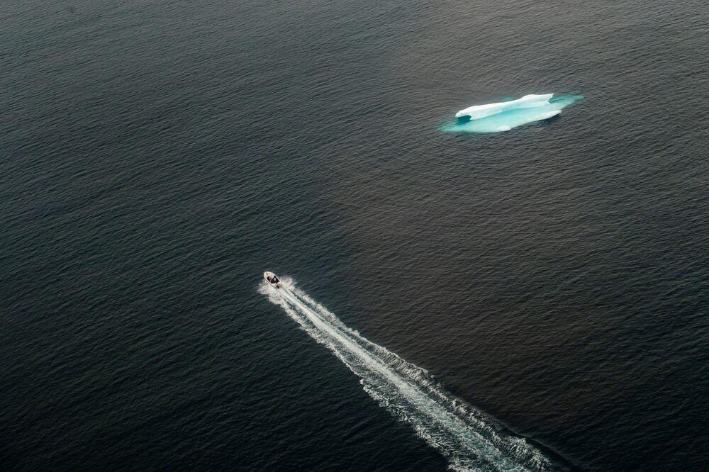 Lancha passa perto de iceberg no oceano perto da cidade de Tasiilaq, na Groenlândia