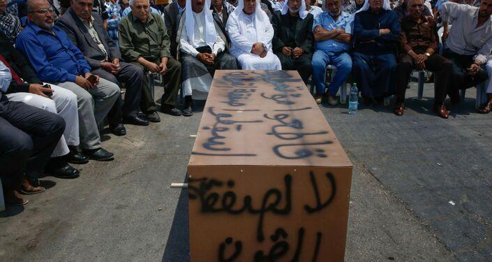 Palestinos sentados perto de um caixão improvisado com palavras Não para o acordo do século, durante protestos contra encontro liderado pelos EUA em Bahrein sobre conflito palestino-israelense, na aldeia de Yatta, perto da Cisjordânia, 24 de junho de 2019