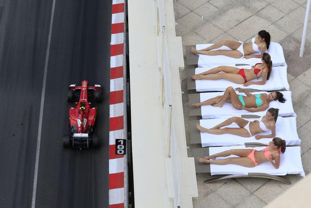 Jovens tomam banho de sol durante corrida em Monte Carlo, Mônaco