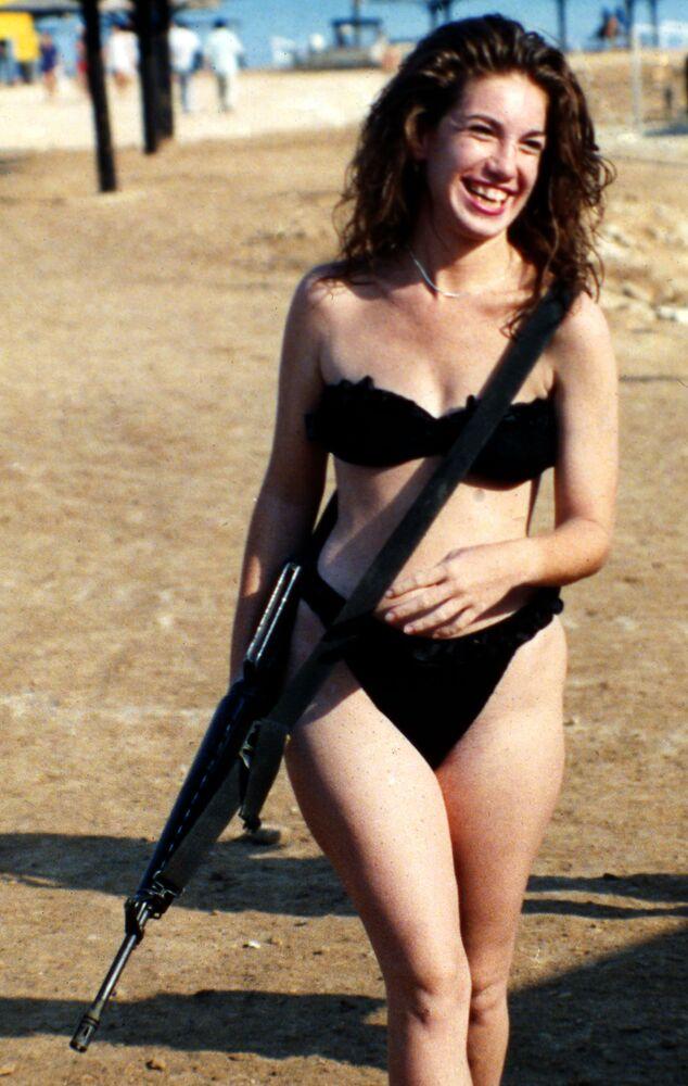 Jovem de biquíni com arma automática na praia em Ein Fashk, Israel