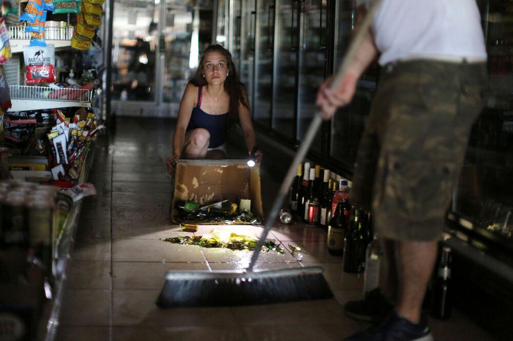 Kaitlin Alexander remove garrafas quebradas de um supermercado após o terremoto