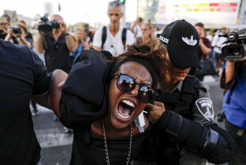Policial israelense detém manifestante durante desfiles contra a brutalidade policial em Tel Aviv, Israel