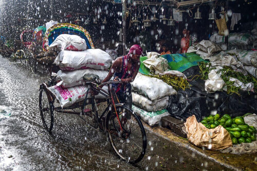 Homem caminha com ciclo-riquixá debaixo de chuva forte em Dhaka, Bangladesh, 30 de junho de 2019