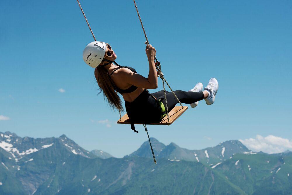 Jovem passeia em balanço na estância de esqui Rosa Khutor, em Sochi, Rússia
