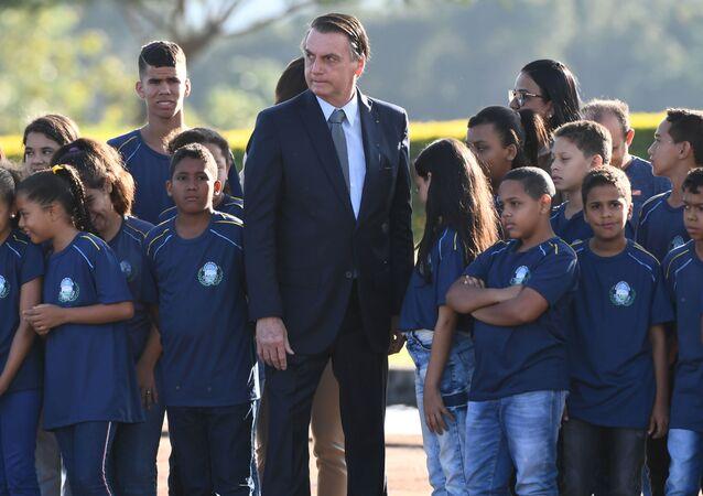 Presidente do Brasil, Jair Bolsonaro, rodeado por crianças durante cerimônia de hasteamento da Bandeira Nacional no Palácio da Alvorada, Brasília, 21 de maio de 2019