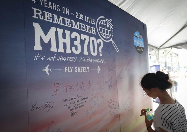 Uma mulher escreve condolências no Dia da Memória dos trágicos acontecimentos com o avião MH370 em Kuala Lumpur