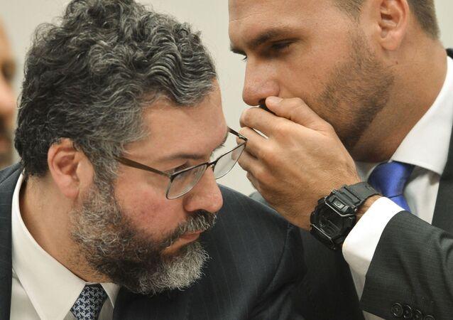 Ministro das Relações Exteriores, Ernesto Araújo, escuta cochicho do deputado Eduardo Bolsonaro (PSL-SP) durante Comissão de Relações Exteriores da Câmara dos Deputados, Brasília, 27 de março de 2019