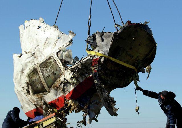 Trabalhadores locais transportam pedaço de destroços do voo MH17 da Malaysia Airlines no local do acidente no leste da Ucrânia, 20 de novembro de 2014