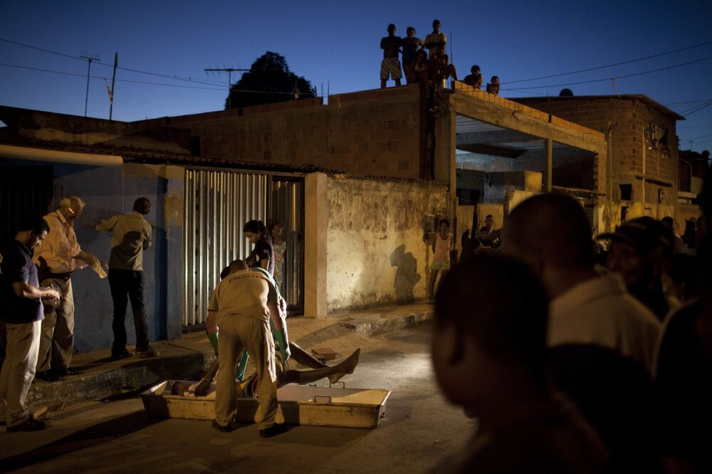 Funcionários da morgue recolhem o corpo de um homem morto durante tiroteio no bairro de Itinga em Salvador, Brasil