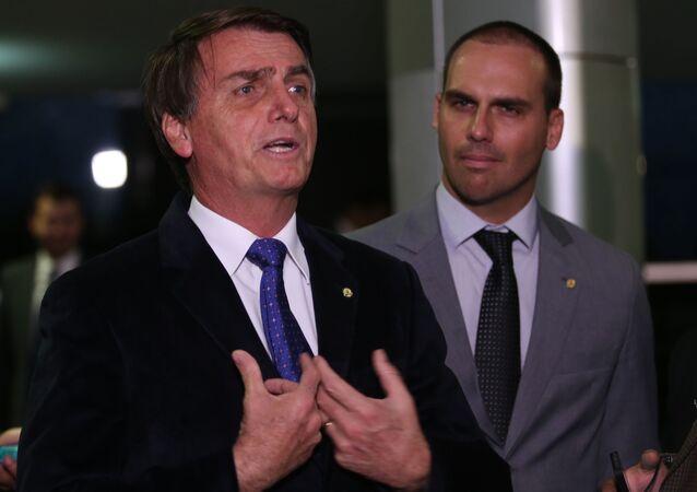 Os deputados Jair Bolsonaro e Eduardo Bolsonaro falam com a imprensa. Foto de 26 de junho de 2016.