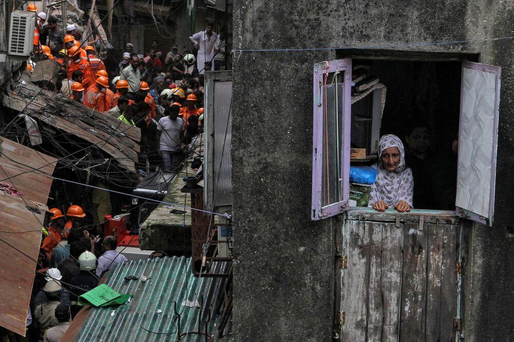 Habitante local olhando pela janela enquanto socorristas procuram sobreviventes após o colapso de um prédio em Mumbai, na Índia