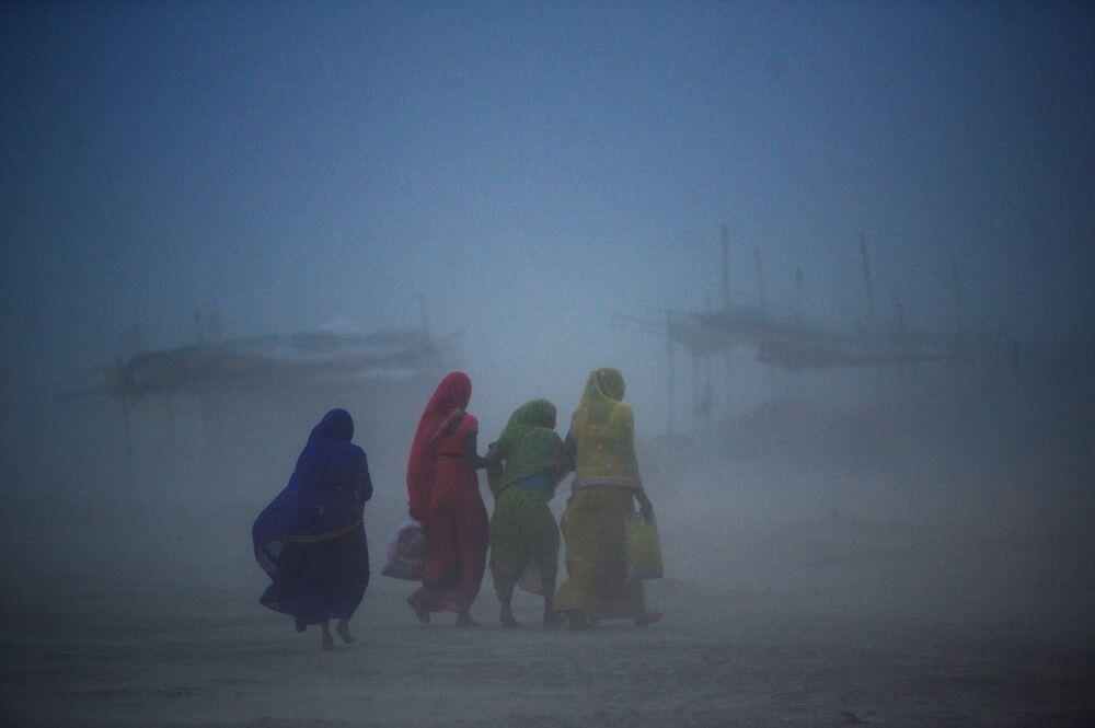 Mulheres atravessando tempestade de areia em Allahabad, na Índia