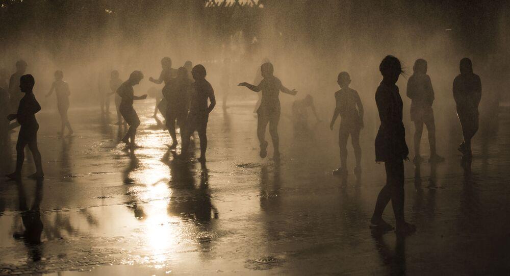 Habitantes se banham em uma fonte no parque Madrid Rio, em Madri, junho de 2019