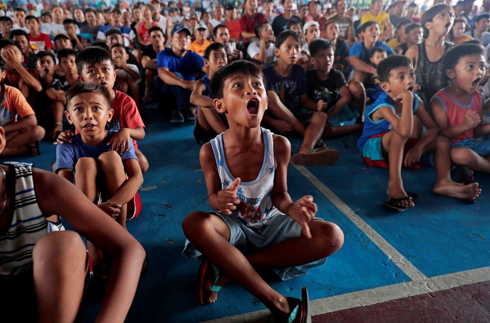 Crianças assistem uma partida de boxe em Marikina, Filipinas