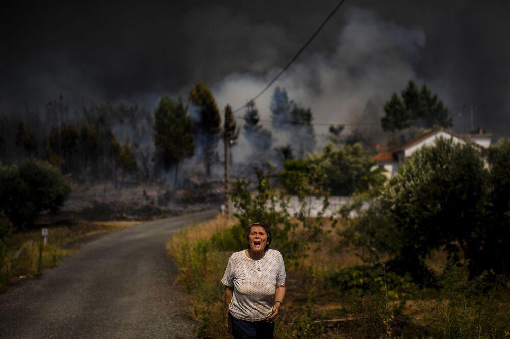 Mulher grita enquanto fogo consome casas residenciais em Casas da Ribeira, Mação, Portugal