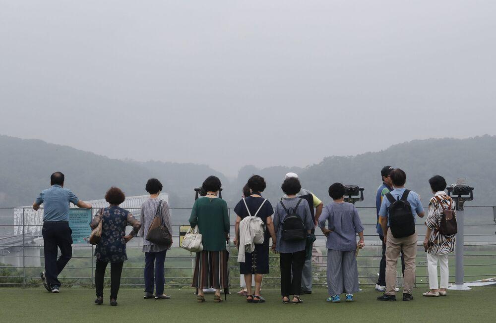 Visitantes observando o lado norte-coreano desde o pavilhão Imjingak em Paju, Coreia do Sul
