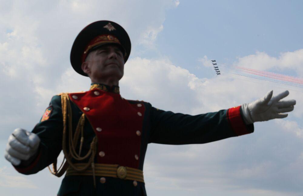 Membro de uma banda militar atua enquanto aviões de caça russos voam em formação durante o desfile do Dia da Marinha na cidade russa de Kronstadt, perto de São Petersburgo, 28 de julho de 2019