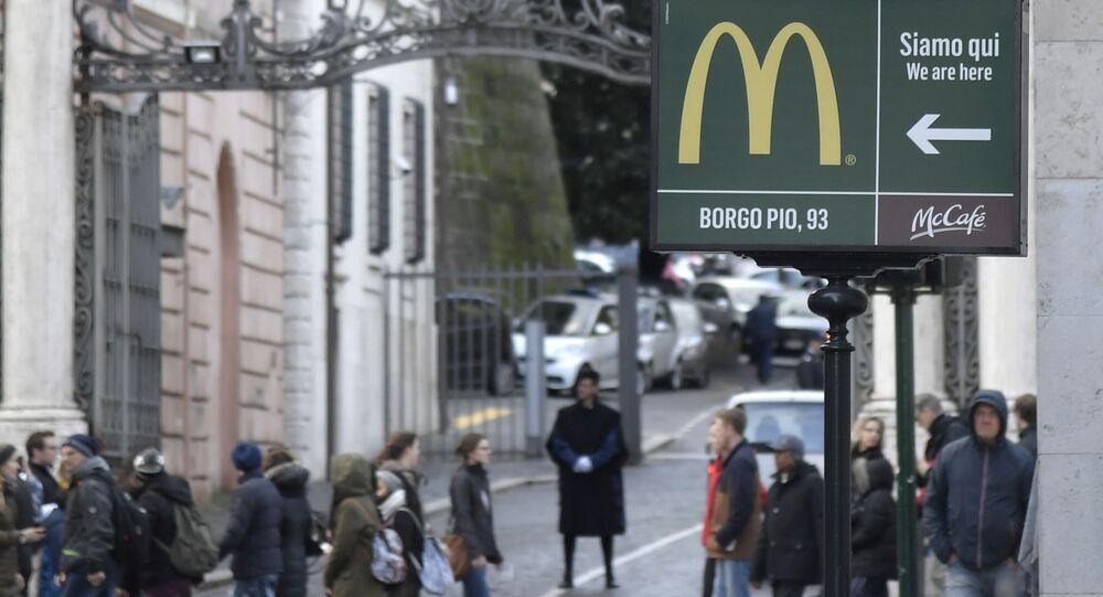 Uma placa mostra o caminho para um restaurante do McDonald's perto de uma entrada para o Vaticano, ao fundo, em Roma (arquivo)
