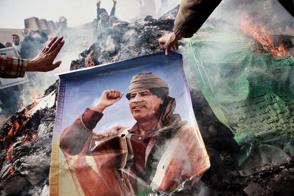 Moradores de Benghazi queimam retrato de Kadhafi, cartazes com citações dele e seu Livro Verde