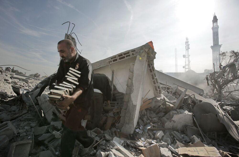 Homem remove pilha de livros do Alcorão de prédio destruído por explosão, Gaza